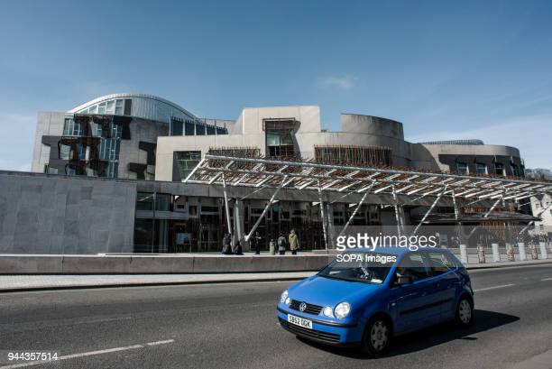 A blue car in front of the Scottish Parliament Building Edinburgh is a city with a population of 500000 in 2017 it the capital city of Scotland...