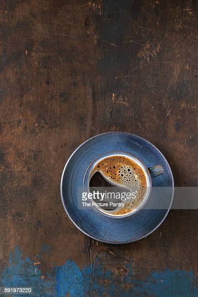 Blue ceramic cup of black hot coffee on saucer, served over old wooden textured background. Simple minimalist style. Top view. Copy space