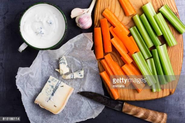 blue cheese dip sauce with celery and carrot sticks - blauwschimmelkaas stockfoto's en -beelden