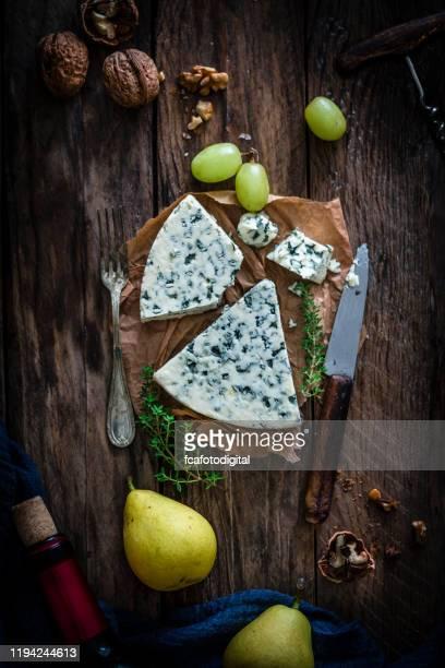 blauwe kaas op rustieke houten tafel - blauwschimmelkaas stockfoto's en -beelden