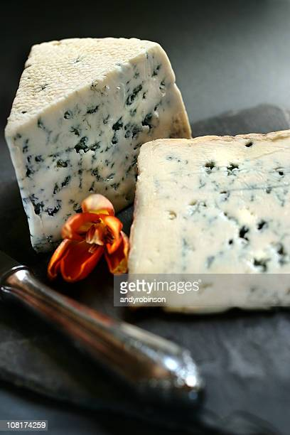 blue cheese sitting on slate board with knife - blauwschimmelkaas stockfoto's en -beelden