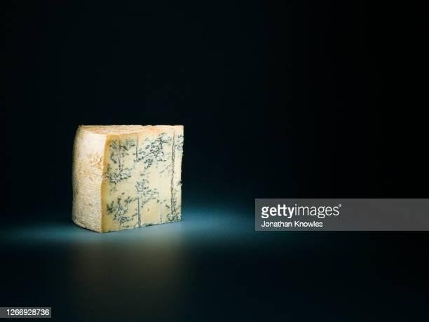 blue cheese under spotlight - blauwschimmelkaas stockfoto's en -beelden