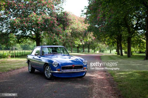 a blue classic car parked on a pretty leafy lane, in horsham, west sussex, uk. - vintage car stock pictures, royalty-free photos & images
