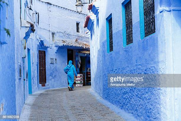 Blue cloaked woman walks through blue streets
