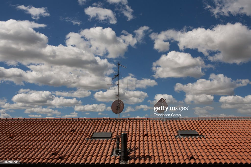 blue cloudy sky over a red roof : Stock-Foto