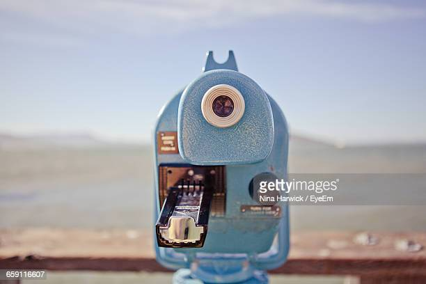 Blue Coin-Operated Binocular At Sea Shore Against Sky