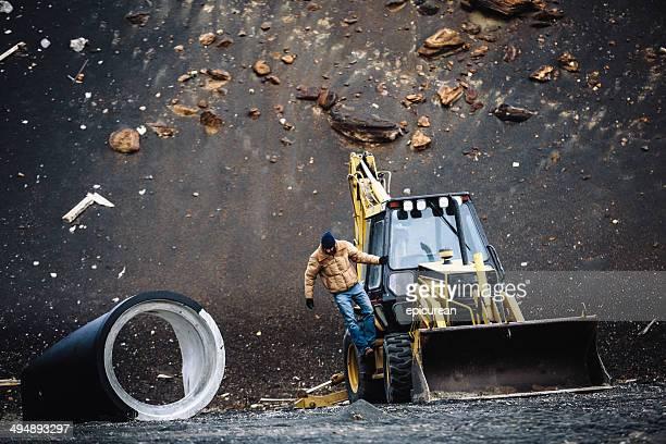 Blue-Collar worker Klettern out backhoe auf Baustelle