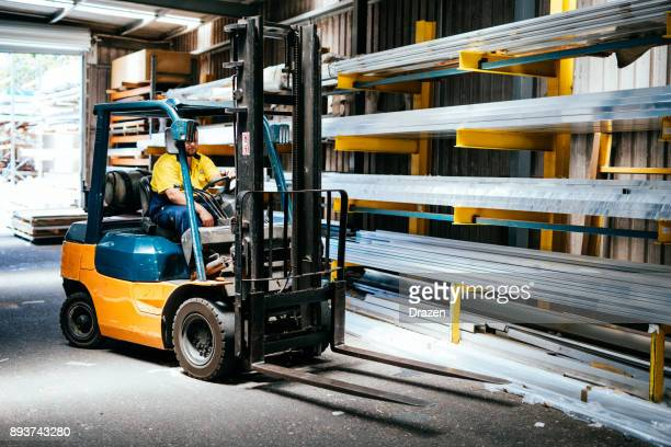 Blue collar worker driving forklift in warehouse