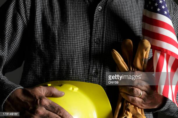 Blue collar worker holding American flag and hard hat
