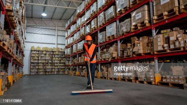 blue collar worker sweeping a distribution warehouse with an industrial broom - sweeping stock pictures, royalty-free photos & images