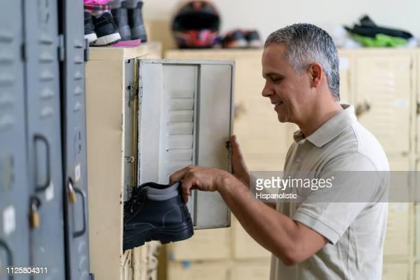 arbeiterin herausnehmen seine arbeit stiefel aus locker zu arbeiten - umkleideraum stock-fotos und bilder