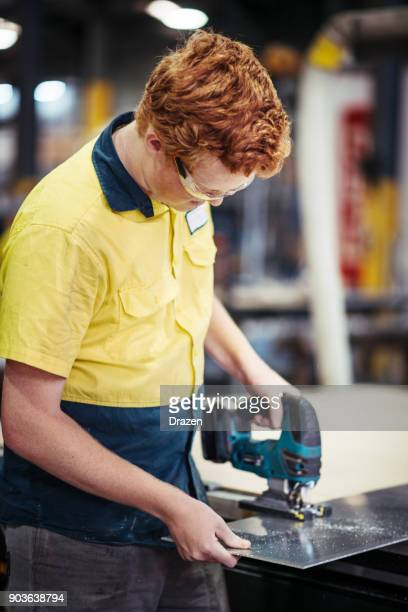 Blue collar worker with electric sawer in factory