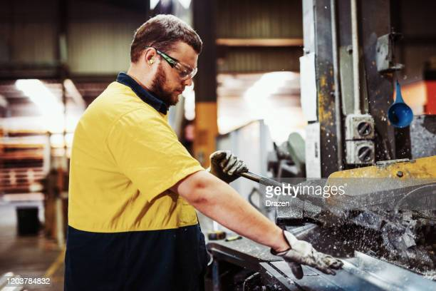 blue collar workers in industry - grinding and cutting metal bars - making stock pictures, royalty-free photos & images
