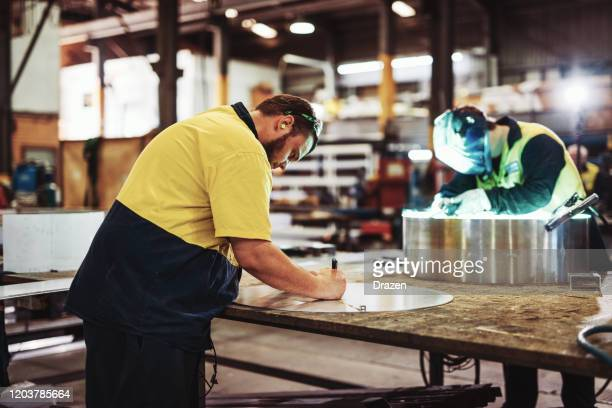 blue collar workers in industry - welding and metal cutting - traditionally australian stock pictures, royalty-free photos & images