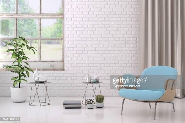 Sillón color azul con mesa de café, flores y plantilla para la pared en blanco