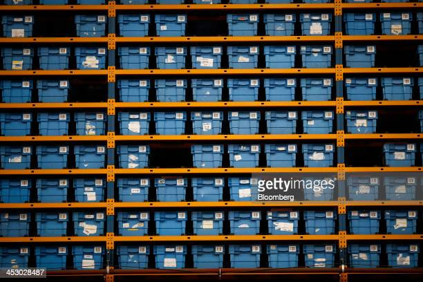 Blue crates containing retail goods sit in orange storage racks on the semiautomated processing line at an Argos goods distribution center operated...