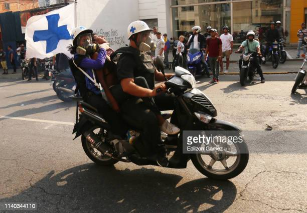 Blue cross volunteers carry a wounded person after the clash between proGuaidó civilians and proMaduro military forces on April 30 2019 in Caracas...