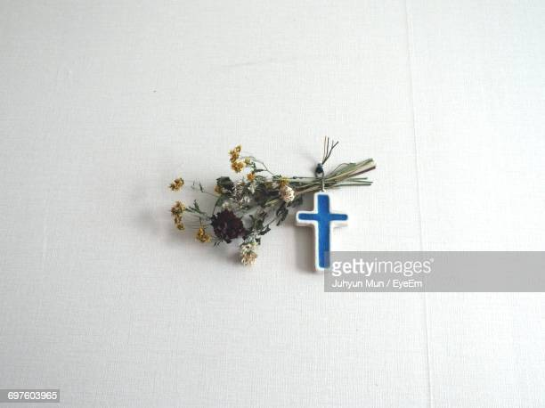 blue cross with flowers hanging on white wall - crosses with flowers stock pictures, royalty-free photos & images