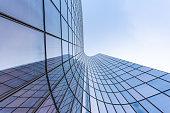 Blue curved glass skyscraper facade against sky