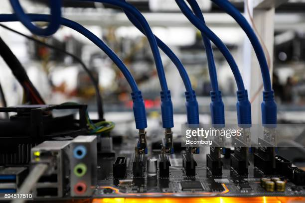 Blue data connector cables are attached to a circuit board at a cryptocurrency mining facility in Incheon South Korea on Friday Dec 15 2017 Hedge...