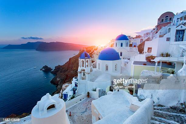 blue domed churches at sunset, oia, santorini - greece stock pictures, royalty-free photos & images