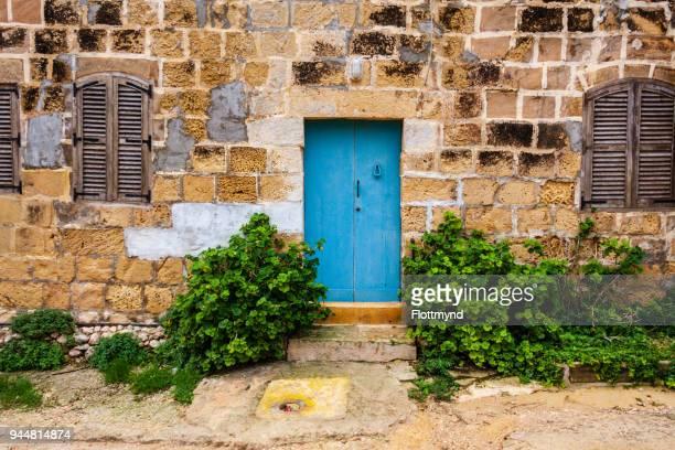 blue door in a weathered house, in gozo, malta - insel gozo malta stock-fotos und bilder