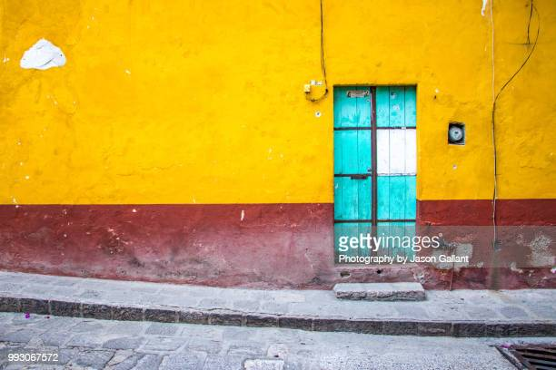 a blue door on a painted wall in san miguel de allende, mexico. - mexiko stock-fotos und bilder