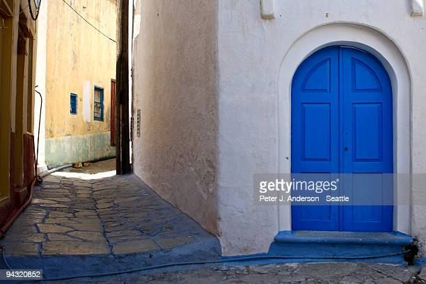 blue door on a white building in greece - symi stock photos and pictures