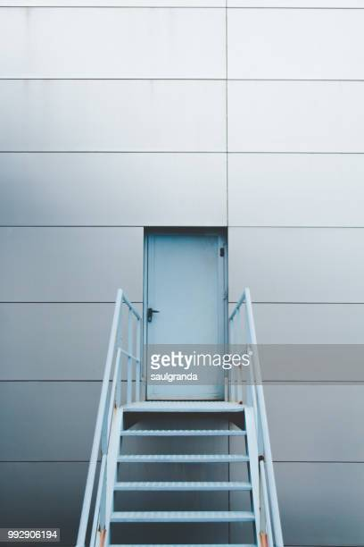 Blue door with stairs against metallic wall
