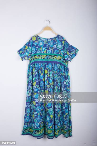 blue dress hanging against white background - floral pattern dress stock pictures, royalty-free photos & images