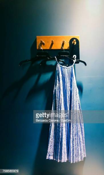 blue dress hanging on coathanger from hook on wall - blue dress stock pictures, royalty-free photos & images
