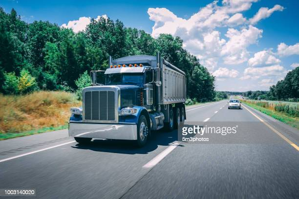 blue dump truck on the highway - dump truck stock pictures, royalty-free photos & images