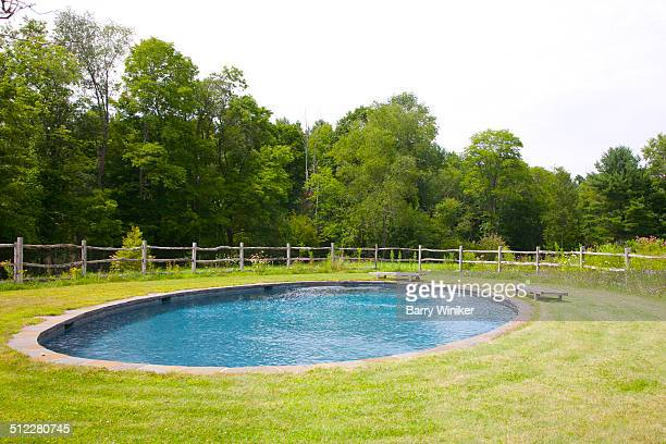Blue elliptical pool set into grass