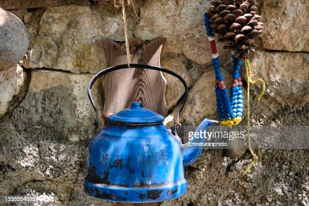 blue enamel teapot hanging on the wall. - emreturanphoto stock pictures, royalty-free photos & images