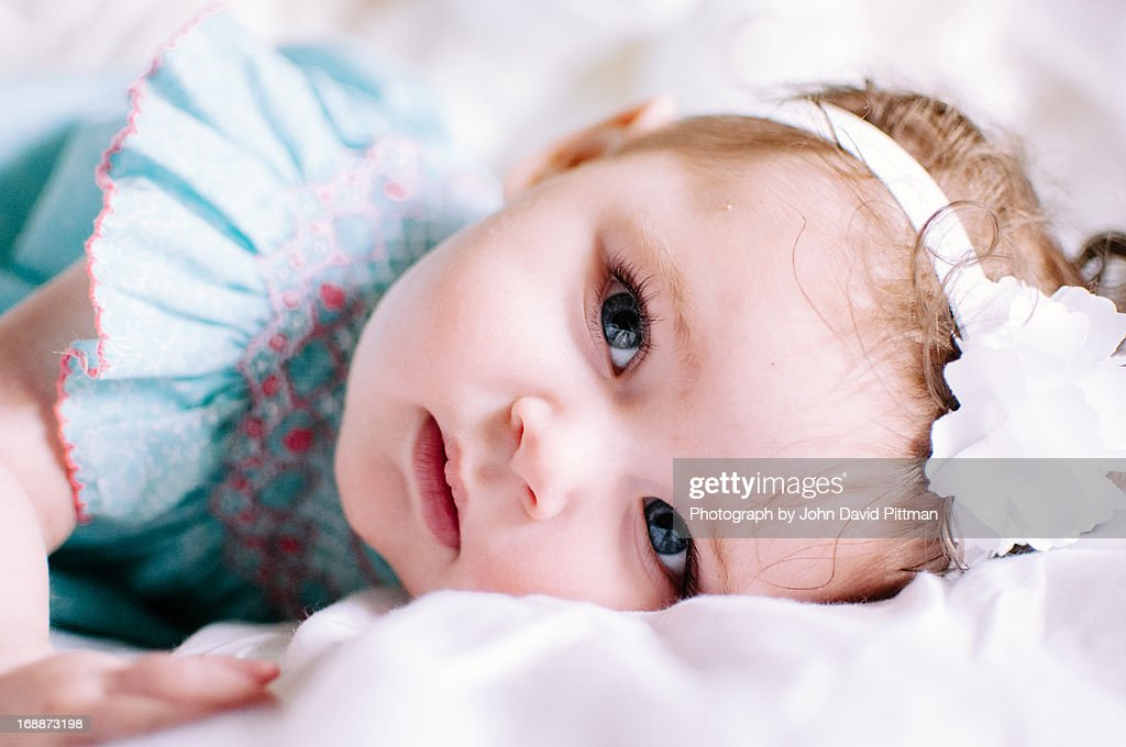 Blue Eyed Baby Girl Lying Down : Stock Photo
