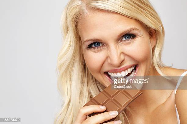 Blue eyed woman enjoying her chocolate bar