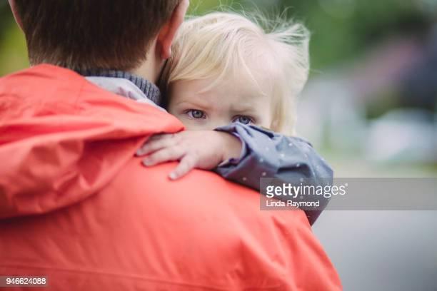 Blå ögon av en liten blond flicka tittar över pappas axel