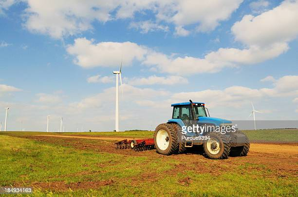 blue farm tractor and cultivator with wind turbine south dakota - tiller stock photos and pictures