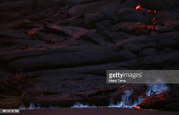 Blue flames of methane gas escape from a crack near a Kilauea volcano fissure in Leilani Estates on Hawaii's Big Island on May 23 2018 in Pahoa...