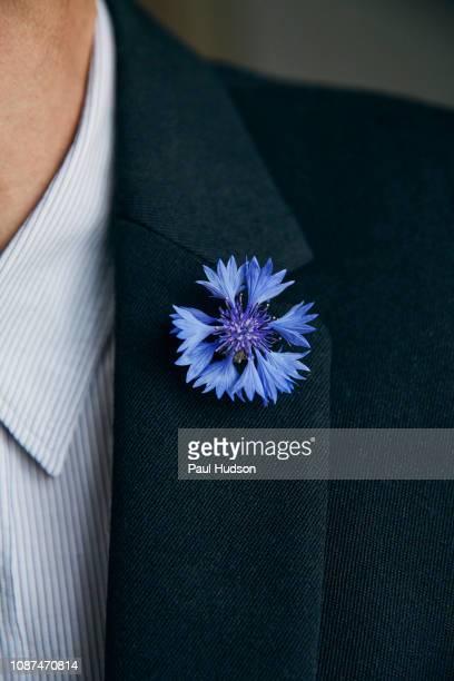 blue flower pin on mans lapel - revers stock-fotos und bilder