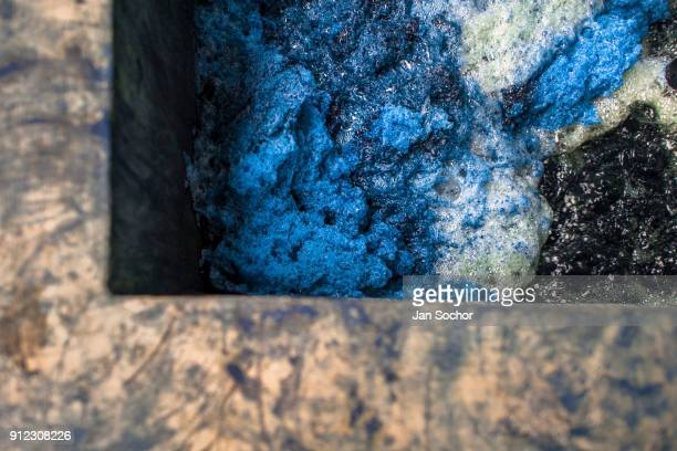 A blue foam is seen at the top of the water solution containing indigo while being stirred in a concrete tank at the semiindustrial manufacture near...