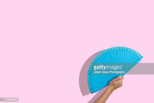 blue folding fan over pink background - hand fan stock pictures, royalty-free photos & images