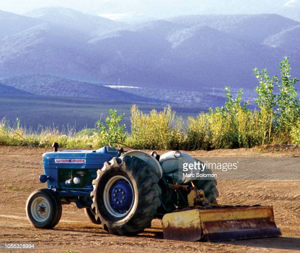 Blue Ford tractor in plowed field