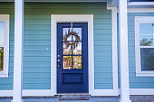 Blue Front Door of a brand new construction house with blue siding, a  ranch style home with a yard