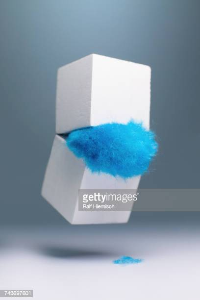 Blue fur falling out from white box against gray background