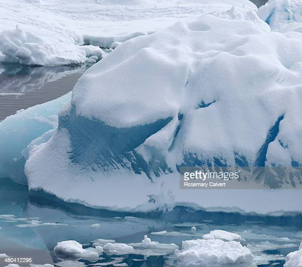 Blue glassy iceberg covered in snow.