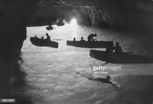 Blue Grotto in Capri, people entering, crouched in rowboats; ghostly interiors, swimmers and rowers silhouetted against phosphorescent water.