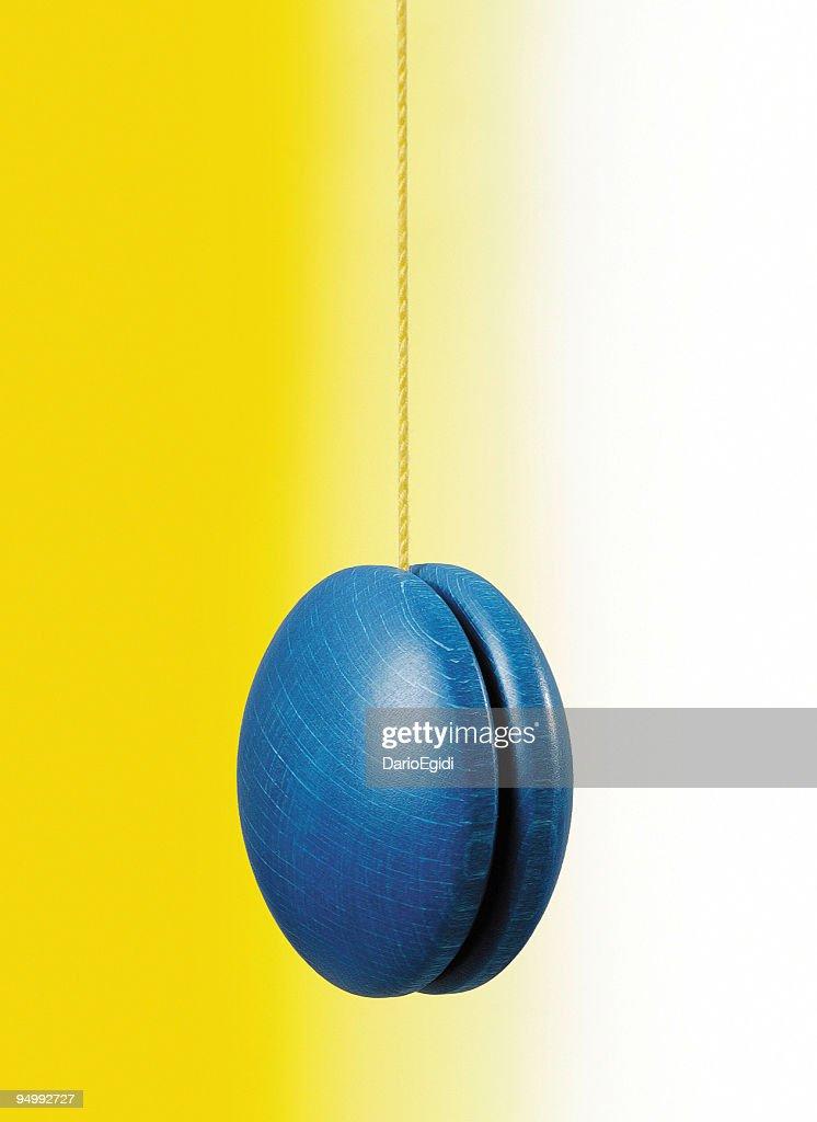 Blue hanging yo-yo on white and yellow background : Stock Photo