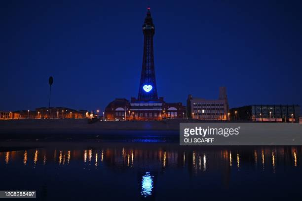 TOPSHOT A blue heart is lit up on the tower in Blackpool northwest England on March 26 as a sign of public admiration for the National Health Service...
