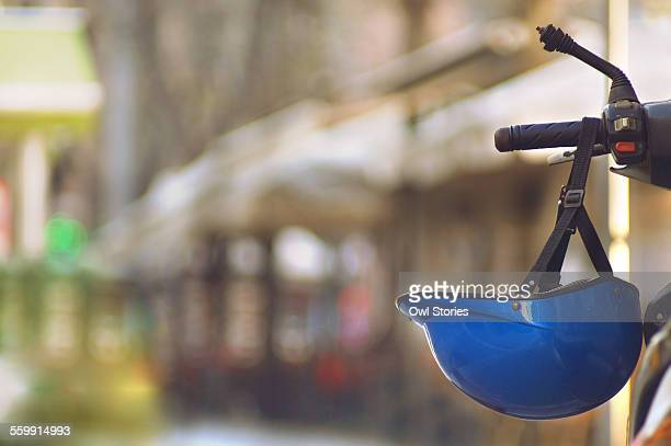 Blue helmet hanging from scooter handle